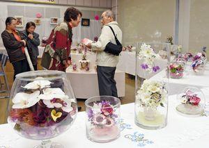 ガラス容器に四季の花を閉じ込めたボトルフラワー作品が並ぶ=佐賀市のアバンセ