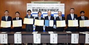 鳥栖市役所で開かれた包括連携協定の締結式。右から4人目が橋本康志市長