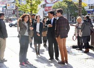 山口祥義知事が県知事役としてアナンダ・エヴァリンハムさん(右)とピムチャノック・ルーウィサートパイプーンさんと共演したワンシーン=佐賀市の駅前まちかど広場