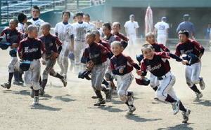 初優勝を果たし、笑顔でスタンドへ走り出す三根ボーイズの選手たち=佐賀市のみどりの森県営球場