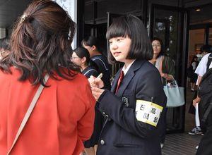 来場者にインタビューする白石高新聞部2年の安井悠さん(右)=佐賀市文化会館