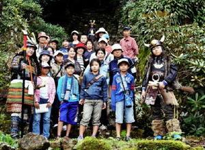 こけむした唐船城祉二の丸へ上がる石階段で記念撮影する参加者=有田町