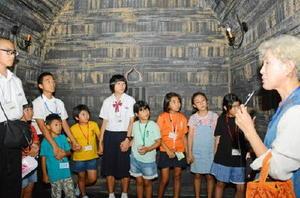 武寧王の墓の内部を再現した展示室でガイドの解説を聞く児童生徒=中清南道公州市の熊津百済文化歴史館