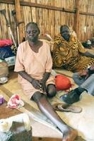 南スーダン・ジュバの避難民キャンプで取材に答えるニャヤト・オロックさん(左)。被弾した左脚は切断された=23日(共同)