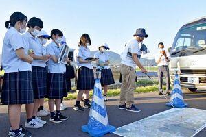 昨年8月の佐賀豪雨の被害などについて大串浩一郎教授(中央)から説明を受ける生徒=大町町福母の大町橋付近