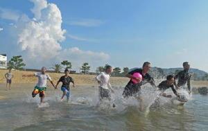 部活動を終えて、入道雲が浮かぶ海に飛び込む中学生=唐津市浜玉町の浜崎海水浴場