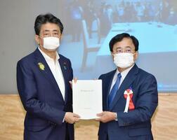 規制改革推進会議の小林喜光議長(右)から答申書を受け取る安倍首相=2日午後、首相官邸
