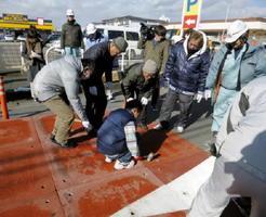 北川副地区の市道に自動車の速度を抑制するハンプ(段差)を設置する地域住民(1月、提供)