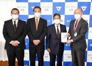 橋本市長(右)に目録を渡した(右2人目から)林社長、迎常務、中尾部長=鳥栖市役所