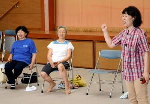 音楽に合わせて体を動かす健康づくりを指導した林加代子さん(右)=吉野ヶ里町のきらら館