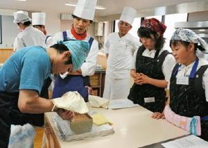フランスの焼き菓子「サンマルク」の作り方を指導する田中昌信さん(右から3人目)。高校生らが仕上げに取り組んだ=佐賀市の西九州大学佐賀調理製菓専門学校