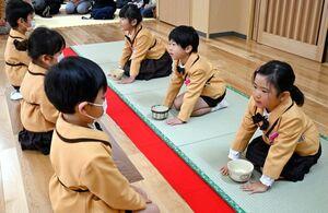 亭主と客に分かれ、作法に従いお茶を味わう園児たち=佐賀市の南部保育園