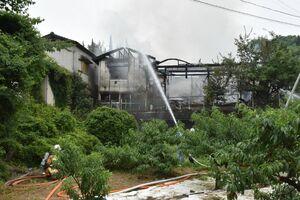 煙を上げる建物に放水する消防関係者=17日午前9時50分ごろ、小城市牛津町下砥川