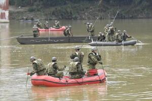 福岡県朝倉市の筑後川で行方不明者を捜索する自衛隊員=24日午前