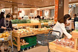 プレオープンした店内で、野菜を手に取る買い物客=佐賀市駅前中央のコムボックス佐賀駅前