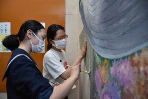 筆や手で壁に色を塗る美術部員たち=多久市の東原庠舎中央校