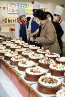 会場に並ぶケーキから、お気に入りをじっくり選ぶ購入者たち=佐賀市多布施の西九州大学佐賀調理製菓専門学校
