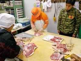 捕まえたイノシシを食肉処理する上峰町の有害駆除捕獲隊員ら=鳥栖市