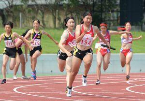 陸上女子400メートルリレー決勝 佐賀北の3走白水莉子(手前左)からバトンを受け、勢いよく走りだすアンカーの森田彩楠(同右)=佐賀市のSAGAサンライズパーク陸上競技場