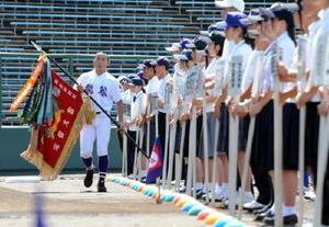 第98回全国高校野球選手権佐賀大会が開幕。開会式では全選手が見つめる中、前年優勝した龍谷の久野隼輝主将(左)が優勝旗を返還した=みどりの森県営球場