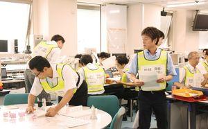 集約した情報を地図上に落とし込む職員(左)=佐賀県庁
