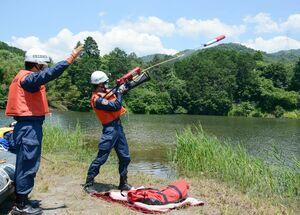 水上にいる要救助者に救命具を発射する消防隊員ら=神埼市神埼町尾崎の天神尾池