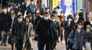 東京・新宿でマスクを着けて歩く人ら=31日夜