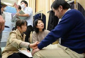 鹿児島地震を想定した演習で、患者役に話を聞く参加者=吉野ヶ里町の肥前精神医療センター