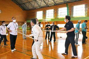 体育施設の防犯訓練で、さすまたの使い方を練習する職員たち=佐賀市の市立体育館