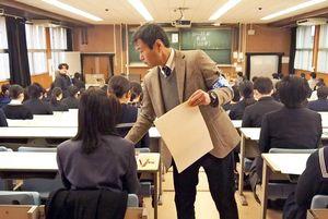 大学職員から問題用紙などを受け取る受験生=佐賀市の佐賀大学本庄キャンパス