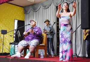 小錦さんの歌に合わせてフラダンスを踊る千絵さん(右)=唐津市浜玉町の旅館魚半