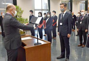 職員提案優秀賞で橋本康志市長から表彰される田中大介さん(右)=鳥栖市役所