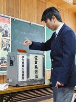 実際に選挙で使う投票箱で投票を体験する伊万里特別支援学校の生徒=伊万里市の同校