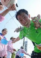 給水所で頭から水をかぶるランナー=神埼市