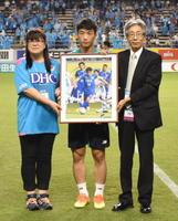 月間MVPに選ばれた鳥栖MF金民友選手(中央)に、記念パネルを贈る光武友子さん(左)。右は佐賀新聞社の井手研一販売局長=鳥栖市のベストアメニティスタジアム