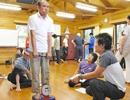 器具を使って背筋力を測る金立水曜登山会のメンバー=今年9月、佐賀市の金立教育キャンプ場