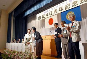 井上節子会長(中央左)がイピル・イピルの会の伊藤登志子代表らに活動資金を手渡す=唐津シーサイドホテル