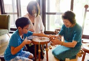 池田ノリさん(右)から教わりながら、組紐でアクセサリーを作る参加者たち=佐賀市の旧久富家