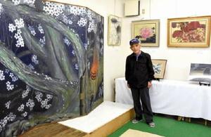 生命の輝きをテーマにした作品が並ぶ。中央は作品展を企画した顕彰会の高森保さん=伊万里市のギャラリー阿亜都
