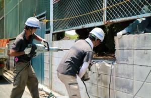 大阪府高槻市の中学校で始まったブロック塀の撤去作業=25日午前