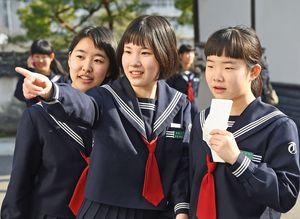 張り出された掲示板に自分の番号を見つけ指さす受験生=鹿島市の鹿島高校