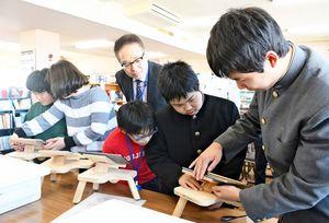 iPad保持台を説明する佐賀工業高の生徒(右)=佐賀市の県立盲学校