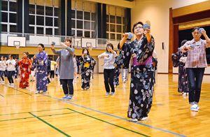 小皿を打ち鳴らしながら舞う4区踊り隊メンバー=有田中体育館