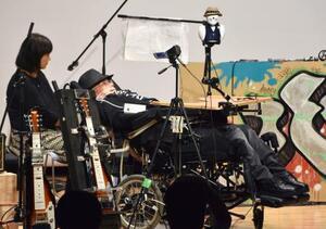 千葉県市川市で開いたコンサートで、災害時の電源確保の重要性を訴える舩後靖彦参院議員(右)=15日午後