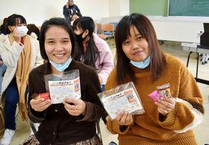 学校と「はっぴぃ〓かむかむ」からお菓子とたまねぎスープのプレゼントを受け取り、笑顔を見せる留学生ら=佐賀女子短期大学