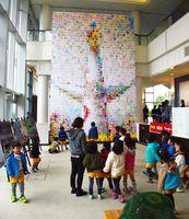 自分たちの塗り絵が使われた太陽の塔のモザイクアートを見る園児ら=有田町の焱の博記念堂