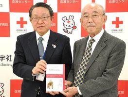 復刻された佐野常民の伝記を受け取った野中源一郎さん(右)。左は日本赤十字社県支部の船津定見事務局長=佐賀市の日本赤十字社県支部