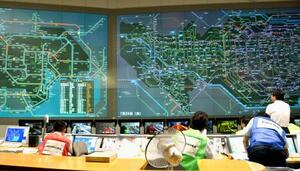 規制の状況を確認する警視庁交通管制センターの担当者=24日午前、東京都港区