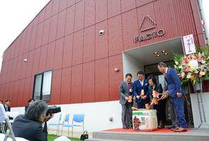 唐津市が整備し、クレコスに貸し出す工場「FACTO」。峰達郎市長や暮部達夫社長らが鏡開きで完成を祝った=唐津市石志