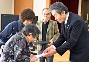 坂本理事長(右)から寄付金を受け取る畑瀬さん